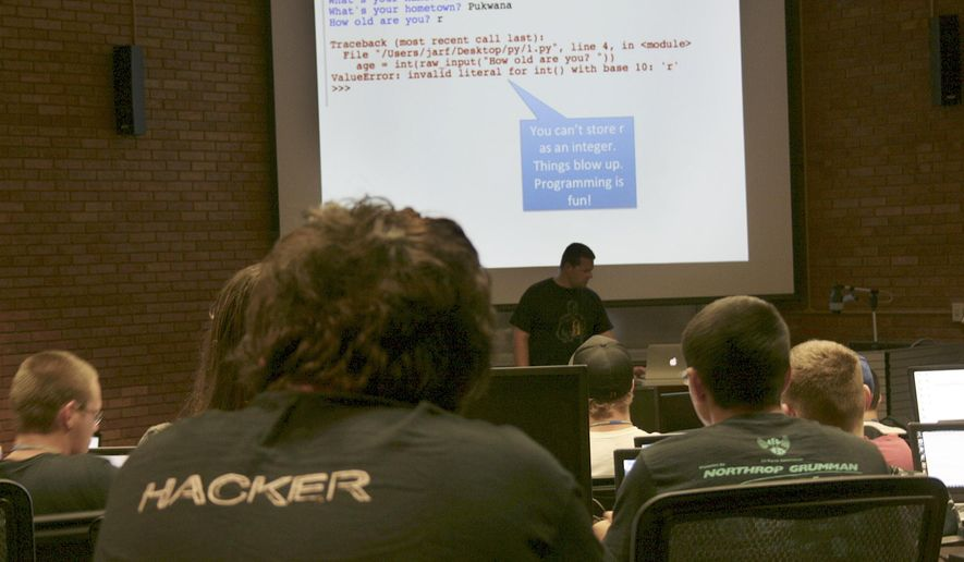 In this July 23, 2014 photo released by Dakota State University, Josh Pauli teaches programming to high school students at the GenCyber Camp on the school's campus in Madison, S.D., It was one of six camps held nationally in 2014 that were funded by the National Science Foundation and National Security Agency. With the increased demand, the NSA and NSF are collaborating to host 43 GenCyber summer camps in around the country in the 2015. (Erica Clements/Dakota State University via AP)