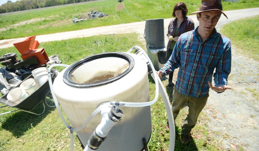 Stewart Lundy explains a specialized microbial inoculant brewed from his farm's composted herbs that he and his wife Natalie McGill use in the process of biodynamic farming at Perennial Roots Farm in Accomac, Va on April 23, 2015.  The husband and wife are biodynamic farmers. The growing movement goes a step beyond organic farming. Like its organic cousins, biodynamic farms eschew genetically modified plants and synthetic pesticides and fertilizers. But they differ by incorporating mysticism and an underlying philosophy that views all components of the farm as a single, living organism. (Jay Diem/The Daily Times via AP)  NO SALES