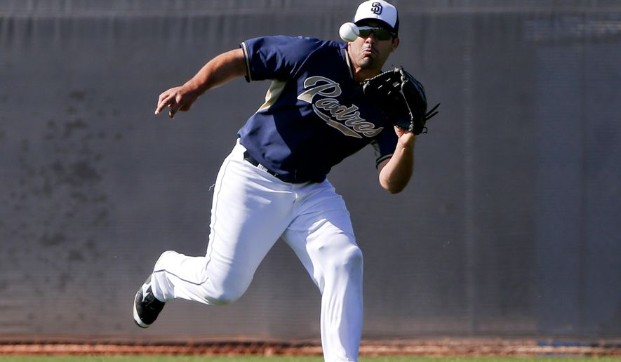 FILE- In this March 23, 2015, file photo, San Diego Padres left fielder Carlos Quentin runs down a line drive during fielding drills for outfielders prior to a spring training baseball game against the Chicago White Sox in Peoria, Ariz.  Quentin retired Friday, May 1, 2015,  after chronic knee injuries cut short his All-Star career. (AP Photo/Lenny Ignelzi, File)