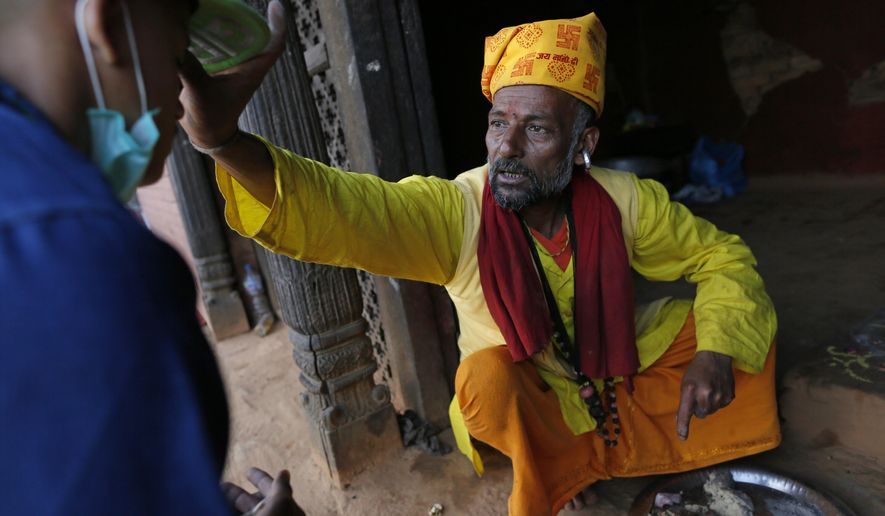 Believing faith in the Hindu gods saved the lives of his village, Hindu priest Ishwar Nath Yogi, 51, blesses followers in the damaged Gorkha Kalika temple in the Pujari village, near the epicenter of last week's massive earthquake, in the Gorkha District of Nepal, Friday, May 1, 2015. (AP Photo/Wally Santana)