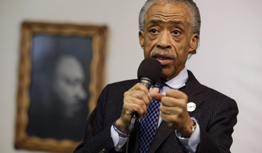 A portrait of the Rev. Dr. Martin Luther King Jr. hangs on the wall behind the Rev. Al Sharpton as he speaks during a rally at the National Action Network, Saturday, May 2, 2015, in New York. (AP Photo/Mary Altaffer)
