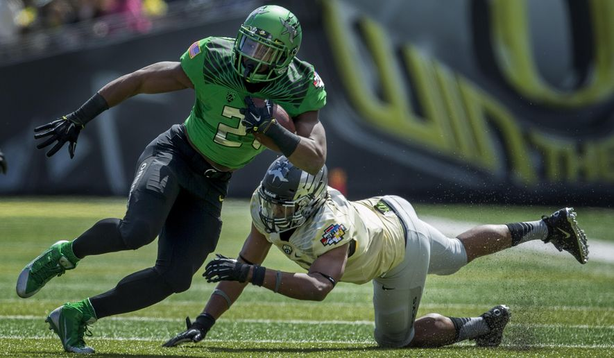 Oregon running back Royce Freeman gets past linebacker Eddie Heard during the spring football game at Autzen Stadium in Eugene, Ore., on Saturday, May 2, 2015. The defending Pac 12 Champions conducted the two-hour intra-squad game in front of more than 35,000 fans.  (Andy Nelson/The Register-Guard via AP)  MANDATORY CREDIT