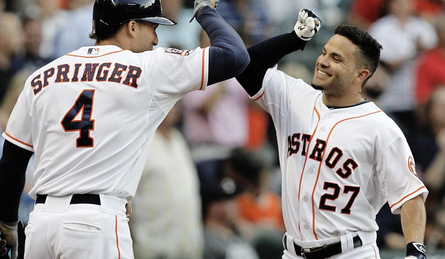 Houston Astros' Jose Altuve (27)fist bumps with George Springer (4) after hitting a three run home run in the fourth inning against the Seattle Mariners in a baseball game Saturday May 2, 2015, in Houston. (AP Photo/Bob Levey)