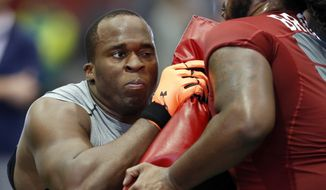Offensive lineman Arie Kouandjio, left, hits a block with Alabama offensive lineman Leon Brown during Alabama's Pro Day, Wednesday, March 11, 2015, in Tuscaloosa, Ala. The event is to showcase players for the upcoming NFL football draft. (AP Photo/Butch Dill)