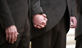 Tim Bostic (left) and Tony London hold hands during the introduction of their wedding ceremony at Christ & St. Luke's Episcopal Church for their wedding ceremony on Saturday, May 2, 2015, in Norfolk, Va. Tim and Tony who have been a couple for 25 years are co-plaintiffs in the case that ultimately granted marriage rights to same sex couples in Virginia. (The' N. Pham/The Virginian-Pilot via AP) **FILE**
