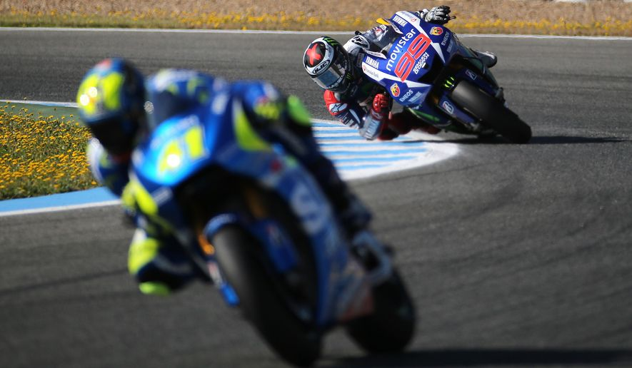 Jorge Lorenzo from Spain and Yamaha, back, races during a free practice session ahead of Sunday's Motorcycle Grand Prix at the Jerez race track in Jerez de la Frontera, southern Spain, Saturday, May 2, 2015. (AP Photo/Miguel Angel Morenatti)