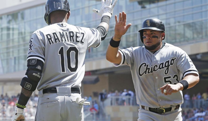 Chicago White Sox' Melky Cabrera, right, is congratulated by Alexei Ramirez after scoring on a hit by Avisail Garcia off Minnesota Twins pitcher Ricky Nolasco in the third inning of a baseball game, Saturday, May 2, 2015, in Minneapolis. (AP Photo/Jim Mone)