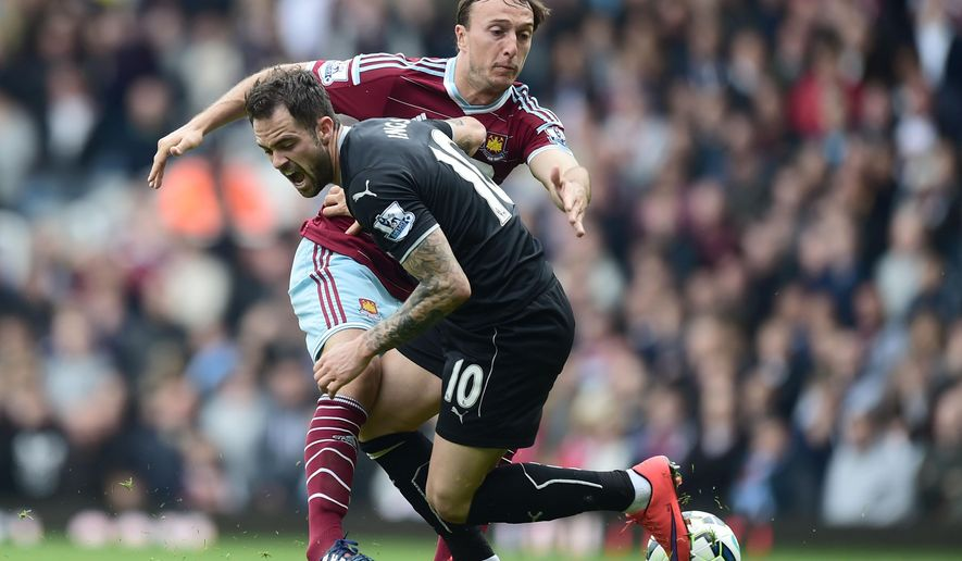 West Ham United's Mark Noble and Burnley's Danny Ings, right, battle for the ball during their English Premier League soccer match at Upton Park, London, Saturday, May 2, 2015. (Adam Davy/PA via AP)      UNITED KINGDOM OUT      -     NO SALES     -     NO ARCHIVES