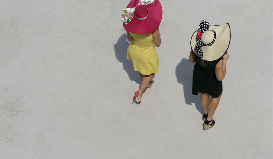 Women make their way to their seats before the 141st running of the Kentucky Derby horse race at Churchill Downs Saturday, May 2, 2015, in Louisville, Ky. (AP Photo/Charlie Riedel)