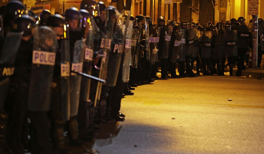 Police in riot gear line up to enforce a curfew imposed in the aftermath of rioting following Monday's funeral for Freddie Gray, who died in police custody, Friday, May 1, 2015, in Baltimore. (AP Photo/David Goldman)