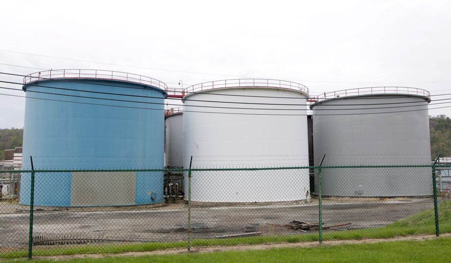 This April 25, 2015 photo shows several large chemical tanks on the grounds of Eagle Natrium LLC Natrium Plant in New Martinsville W.Va.  After a 2014 chemical spill polluted drinking water for thousands in West Virginia, lawmakers mandated tighter surveillance of the state's chemical storage tanks.(AP Photo/Raymond Thompson)