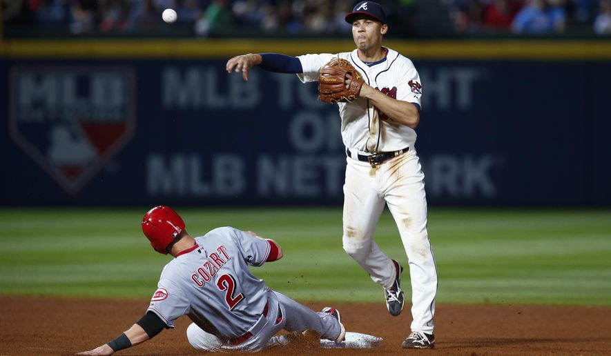 Cincinnati Reds' Zack Cozart is out at second as Atlanta Braves shortstop Andrelton Simmons makes the throw to first in the seventh inning of a baseball game Saturday, May 2, 2015 in Atlanta. The Reds won 8-4. (AP Photo/Kevin Liles)