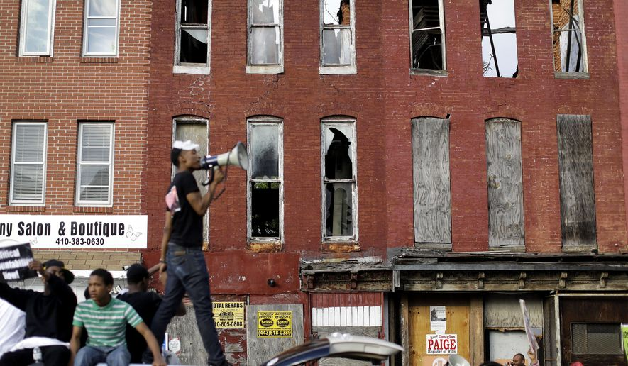 In front of blighted buildings, a protester leads marchers in a chant from atop a vehicle in Baltimore on Saturday, May 2, 2015, a day after charges were announced against the police officers involved in Freddie Gray's death. (AP Photo/Patrick Semansky)