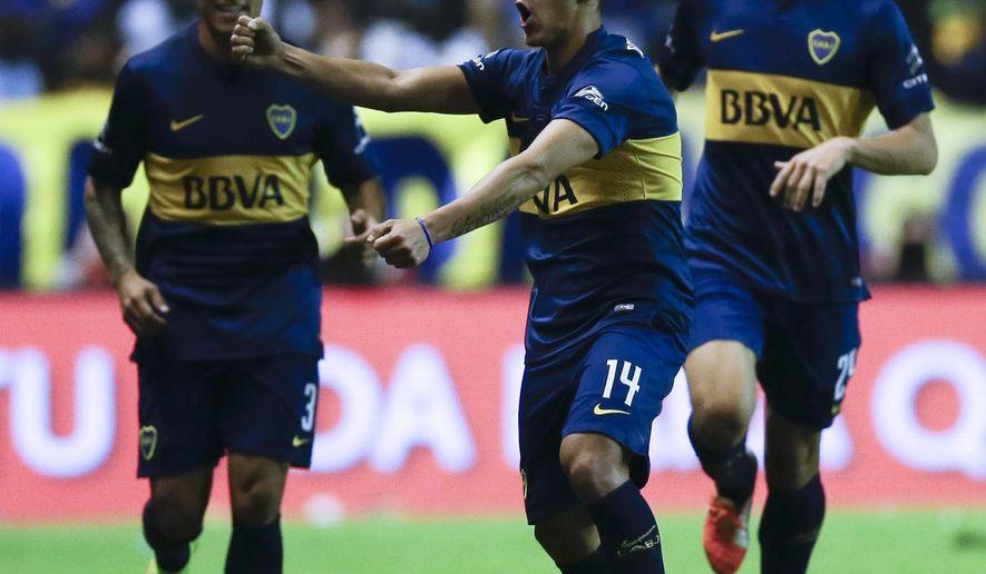 Cristian Pavon of Boca Juniors, center, celebrates scoring against  River Plate during a local tournament soccer match in Buenos Aires, Argentina, Sunday, May 3, 2015.(AP Photo/Natacha Pisarenko)