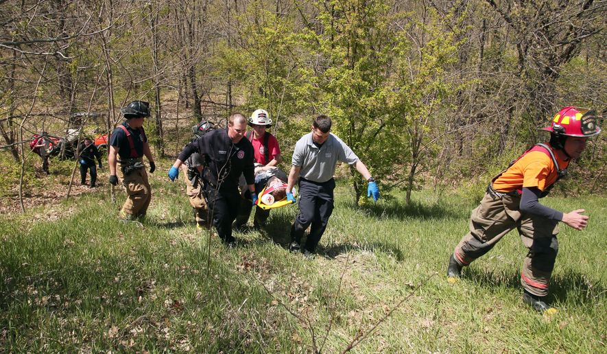 In this April 28, 2015 photo, paramedics from the Ottawa Fire Department and Illinois Department of Conservation Police Officer Phil Wire assist a 21-year-old woman after she fell 21 feet off a ledge at Buffalo Rock State Park in Ottawa, Ill.  Hiking season has barely begun but there have already been three major rescues of trailgoers who have fallen off ridges at or near Starved Rock State Park. In all three cases, the hikers broke park rules by veering off the marked path and climbing sandstone walls before they plummeted.  (Anthony Souffle/Chicago Tribune via AP) MANDATORY CREDIT CHICAGO TRIBUNE; CHICAGO SUN-TIMES OUT; DAILY HERALD OUT; NORTHWEST HERALD OUT; THE HERALD-NEWS OUT; DAILY CHRONICLE OUT; THE TIMES OF NORTHWEST INDIANA OUT; TV OUT; MAGS OUT; NO SALES