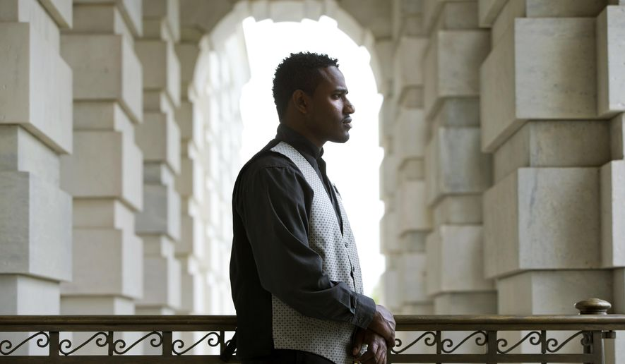 In this photo taken on Friday, May 1, 2015, Abraham Tesfahun, 21, who works in food service at the Senate and makes $10.70 an hour, poses for a portrait at the Capitol in Washington. Income inequality is more than a political sound bite to workers in the Capitol. It's their life. Many of the Capitol's food servers, who make the meals, bus the tables and run the cash registers in the restaurants and carryouts that serve lawmakers, earn less than $11 an hour. Some make nothing at all when Congress is in recess. (AP Photo/Jacquelyn Martin)