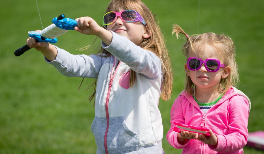 Natalie Cooper 4, left, with sister Evelyn Cooper 2, flying their kite on April 26, 2015 in Papillion, Neb.  National Kite Month, sponsored by the American Kitefliers Association and Kite Trade Association International, runs through May 10. At its heart, the promotion is meant to spread kiting as a hobby through public events and community outreach. (Kent Sievers/The World-Herald via AP) MAGS OUT; ALL NEBRASKA LOCAL BROADCAST TELEVISION OUT