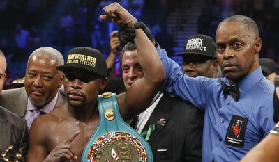 Floyd Mayweather Jr., left, holds up the title belt next to referee Kenny Bayless after his win against Manny Pacquiao, from the Philippines, in their welterweight title fight on Saturday, May 2, 2015 in Las Vegas. (AP Photo/John Locher)