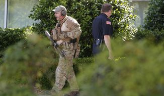 A police officer walks around the perimeter of the Curtis Culwell Center on Sunday in Garland, Texas. A contest for cartoons depictions of the Prophet Muhammad in the Dallas suburb is on lockdown Sunday after authorities reported a shooting outside the building. (Associated Press)