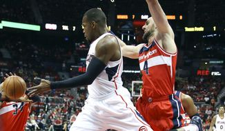 Atlanta Hawks forward Paul Millsap, front,  passes as Washington Wizards center Marcin Gortat, right, defends in the first half of an NBA second-round basketball payoff series game Sunday, May 3, 2015, in Atlanta. (AP Photo/John Bazemore)
