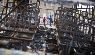 """A couple holds hands while walking past a burnt out van next to the Southern Baptist Church Sunday, May 3, 2015, in Baltimore. A nearby senior center being built by the church burned during the riots following Freddie Gray's funeral. Gov. Larry Hogan has called for a statewide """"Day Of Prayer And Peace"""" on Sunday after civil unrest rocked Baltimore. (AP Photo/David Goldman)"""