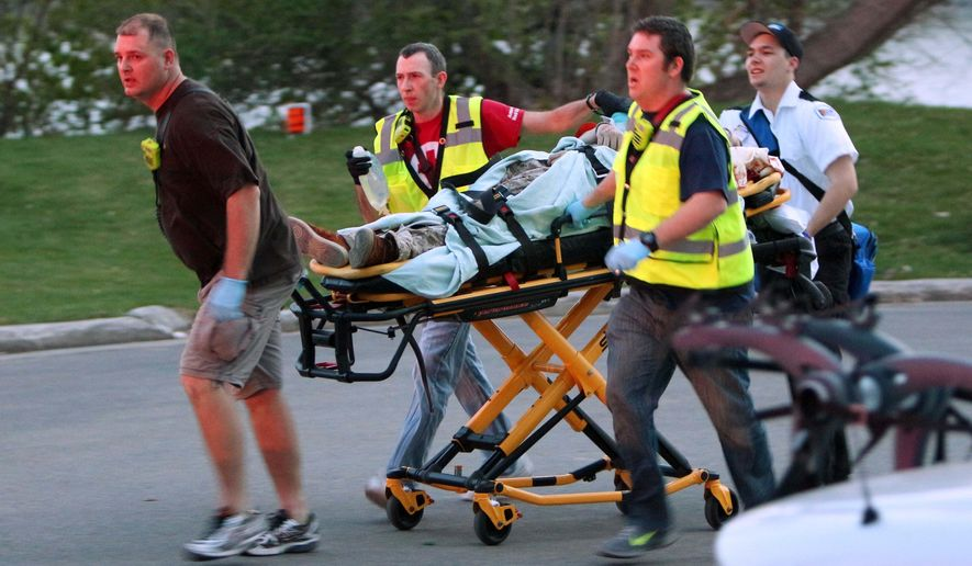In this May 3, 2015 photo, authorities move a shooting victim to an ambulance at the Trestle Trail Bridge in the City of Menasha, Four people are dead and one person is injured after a man opened fire on the bridge in what police describ as a random shooting. (Duke Behnke/The Post-Crescent  via AP)