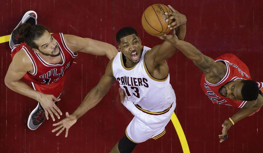 Cleveland Cavaliers center Tristan Thompson (13) fights for a rebound against Chicago Bulls guard Aaron Brooks, right, and center Joakim Noah, left, during the first half of Game 1 in a second-round NBA basketball playoff series Monday, May 4, 2015, in Cleveland. (AP Photo/Tony Dejak)