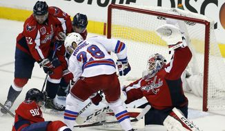 New York Rangers center Dominic Moore (28) is surrounded by left wing Marcus Johansson (90), from Sweden, defenseman Mike Green (52), defenseman Matt Niskanen (2) and goalie Braden Holtby (70) during the third period of Game 3 in the second round of the NHL Stanley Cup hockey playoffs, Monday, May 4, 2015, in Washington. The Capitals won 1-0. (AP Photo/Alex Brandon)
