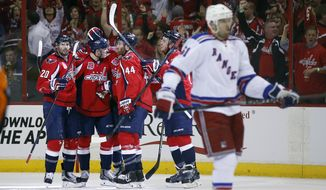 The Washington Capitals celebrate around center Jay Beagle (83) after his goal during the second period of Game 3 in the second round of the NHL Stanley Cup hockey playoffs against the New York Rangers, Monday, May 4, 2015, in Washington. (AP Photo/Alex Brandon)
