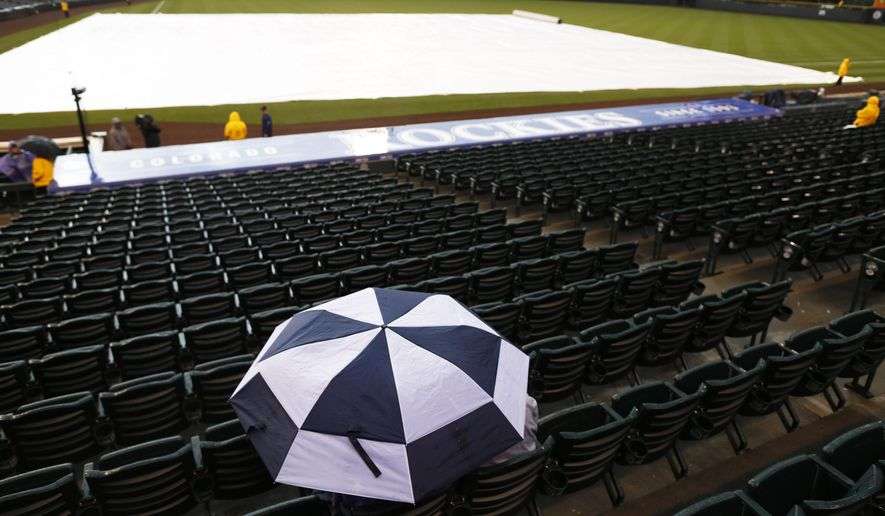 A lone fan seeks cover under an umbrella as a light rain delays the start of the first inning of a baseball game between the Arizona Diamondbacks and the Colorado Rockies Monday, May 4, 2015, in Denver. (AP Photo/David Zalubowski)