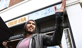 In this Thursday, March 26, 2015, photo, Russell Brand speaks at the opening of The Trew Era Cafe, a social enterprise community project on the New Era estate in east London. Comedian turned political activist Russell Brand has changed his mind and is no longer urging people not to vote in Thursday's general election. Instead, Brand on Monday, May 4, 2015, used his YouTube channel to urge his more than 1 million subscribers to back the Labour Party's Ed Miliband. (Photo by Joel Ryan/Invision/AP) **FILE**