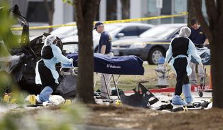 Personnel remove the bodies of two gunmen Monday, May 4, 2015, in Garland, Texas. Police shot and killed the men after they opened fire on a security officer outside the suburban Dallas venue, which was hosting provocative contest for Prophet Muhammad cartoons Sunday night, authorities said. (AP Photo/Brandon Wade)