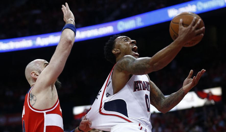 Atlanta Hawks guard Jeff Teague (0) heads to the basket as Washington Wizards center Marcin Gortat (4) defends in the first half of game two of the second-round NBA playoff series basketball game  Tuesday, May 5, 2015, in Atlanta. (AP Photo/John Bazemore)