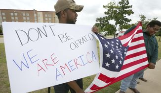 Joseph Offutt, left, and Raheem Peters hold a sign and a U.S. flag across the street from the Curtis Culwell Center, Tuesday, May 5, 2015, in Garland, Texas. A man, whose social media presence was being scrutinized by federal authorities, was one of two suspects killed in the Sunday shooting at this location that hosted a cartoon contest featuring images of the Muslim Prophet Muhammad. The Islamic State group on Tuesday claimed responsibility for the attack. (AP Photo/LM Otero)