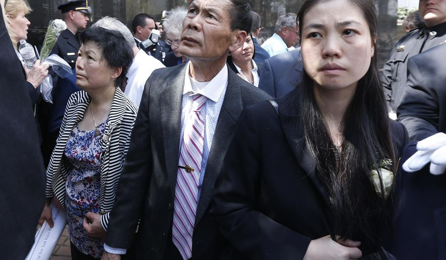 Pei Xia Chen, right, widow of slain New York City Police Detective Wenjian Liu, stands with his parents Xiu Yan Li, left, and Wei Tang Liu after a ceremony at the New York State Police Officers Memorial on Tuesday, May 5, 2015, in Albany, N.Y. They waited as a worker traced Liu's name on paper from the memorial. Eight officers who died last year from line-of-duty injuries have been honored at the memorial, along with 14 who died from illnesses related to recovery work at the World Trade Center destroyed by terrorists in 2001. (AP Photo/Mike Groll)