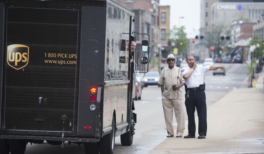 Jeff Hermansen, left, speaks with Lt. Joel Givens after rescuing a man who jumped into the Rock River Tuesday, May 5, 2015, in Rockford, Ill. Authorities are praising the heroism of Hermansen, who risked his life to rescue a man who jumped into a river in Illinois on Tuesday. (Sunny Strader/Rockford Register Star via AP)  MANDATORY CREDIT