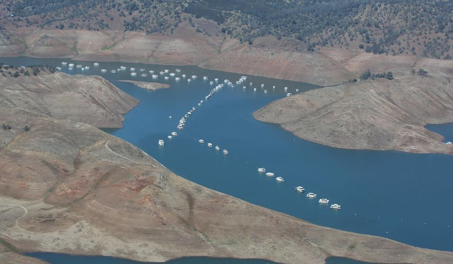 In this aerial photo taken Tuesday, April 28, 2015, house boats sit in the receding waters of New Hogan Lake near Valley Springs, east of Lodi, Calif. The State Water Resources Control Board is considering sweeping mandatory emergency regulations to protect water supplies as water levels as some of California's lakes and reservoirs continue to decline. (AP Photo/Rich Pedroncelli)