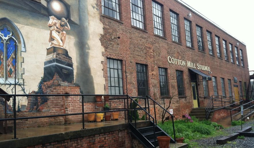 This April 19, 2015 photo shows an old brick building in the River Arts District of Asheville, N.C. Nearly two dozen historic buildings in the neighborhood now house more than 180 artists working in a variety of media, from wood and clay to basketry, painting and textiles. (AP Photo/Beth J. Harpaz)