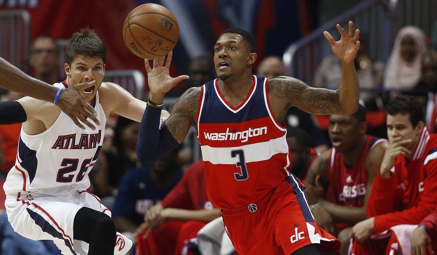 Washington Wizards guard Bradley Beal (3) chases a loose ball as Atlanta Hawks guard Kyle Korver (26) looks on in the first half of game two of the second-round NBA playoff series basketball game, Tuesday, May 5, 2015, in Atlanta. (AP Photo/John Bazemore)