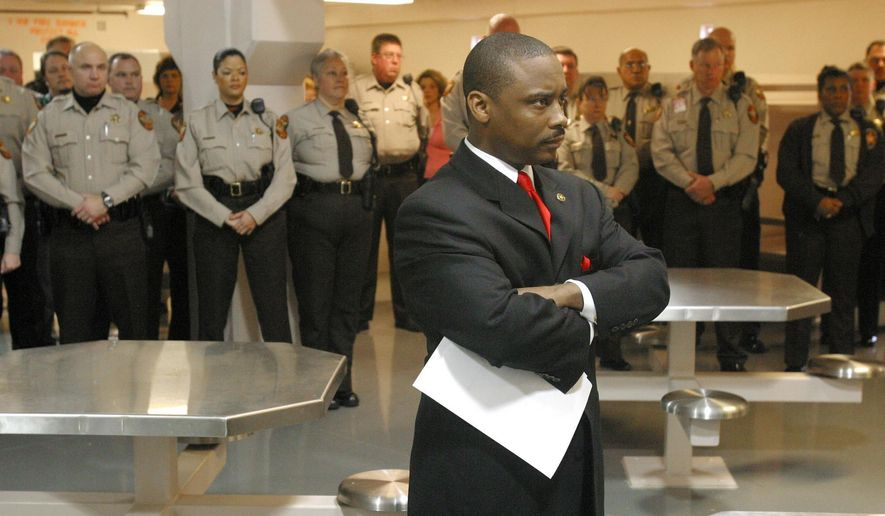 In this Thursday, Jan. 13, 2005, file photo, newly sworn-in Clayton County Sheriff Victor Hill, foreground, stands with arms folded after speaking to his deputies in Jonesboro, Ga. (Zach Porter/Clayton Daily News, File via AP)