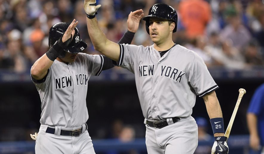 New York Yankees' Mark Teixeira, right, celebrates his two-run homer with teammate Jacoby Ellsbury off Toronto Blue Jays starting pitcher Marco Estrada during the fifth inning of a baseball game Tuesday, May 5, 2015, in Toronto. (AP Photo/The Canadian Press, Frank Gunn)
