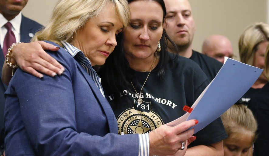 Oklahoma Gov. Mary Fallin, left, and Brandi Dees, right, the widow of Oklahoma State Highway Trooper Nicholas Dees, embrace as they look over a bill banning texting and driving which Fallin signed into law in Oklahoma City, Tuesday, May 5, 2015. Trooper Nicholas Dees was killed and Trooper Keith Burch was injured when they were struck by a vehicle on Interstate 40 in January 2015, whose driver was allegedly updating a social media page at the time. (AP Photo/Sue Ogrocki)