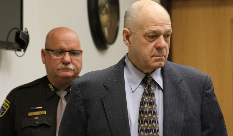 In this photo taken Monday morning, May 4, 2015, defendant Martin Edward Zale, foreground, escorted by Livingston County Sheriff's Deputy Everett DeGrush, walks into the courtroom in Howell, Mich, on Monday morning. He is on trial for murder in connection with a fatal road-rage shooting of Derek Flemming in Genoa Township on Sept. 2. Zale's lawyers said Tuesday, May 5, 2015, that he feared for his life and fired in self-defense after being punched in the jaw.  (Lisa Roose-Church /Livingston County Daily Press & Argus via AP)  NO SALES