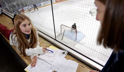 Kim Zeiss, right, helps her daughter, Madison, 10, with her homework as Kim's son, Jake, 9, practices goal keeping with the Junior Kings hockey team Friday, Jan. 14, 2005, at Health South training facility in El Segundo, Calif. The Zeiss family is one of 32 Los Angeles families in a study of the modern American family by UCLA scientists. (AP Photo/Kevork Djansezian)