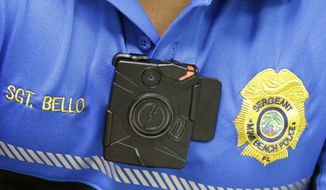 Miami Beach Police Sgt. Alex Bello, in charge of the department's body camera program, wears a body camera during a demonstration at a news conference, Tuesday, May 5, 2015, in Miami Beach, Fla. Ten police motorcycle officers will be issued body cameras Tuesday, with a total of 30 officers by the end of the month in a three-month pilot program to test the technology. (AP Photo/Wilfredo Lee)