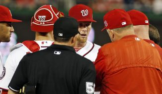 Washington Nationals starting pitcher Stephen Strasburg, center, talks with pitching coach Steve McCatty, second from right, and manager Matt Williams, right, as they come to the mound to check on Strasburg during the second inning of a baseball game against the Miami Marlins at Nationals Park, Tuesday, May 5, 2015, in Washington. Strasburg was relieved in the third inning. (AP Photo/Alex Brandon)