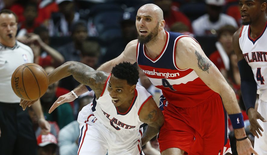 Atlanta Hawks guard Jeff Teague (0) chases a loose ball with Washington Wizards center Marcin Gortat (4) in the first half of game two of the second-round NBA playoff series basketball game  Tuesday, May 5, 2015, in Atlanta. (AP Photo/John Bazemore)