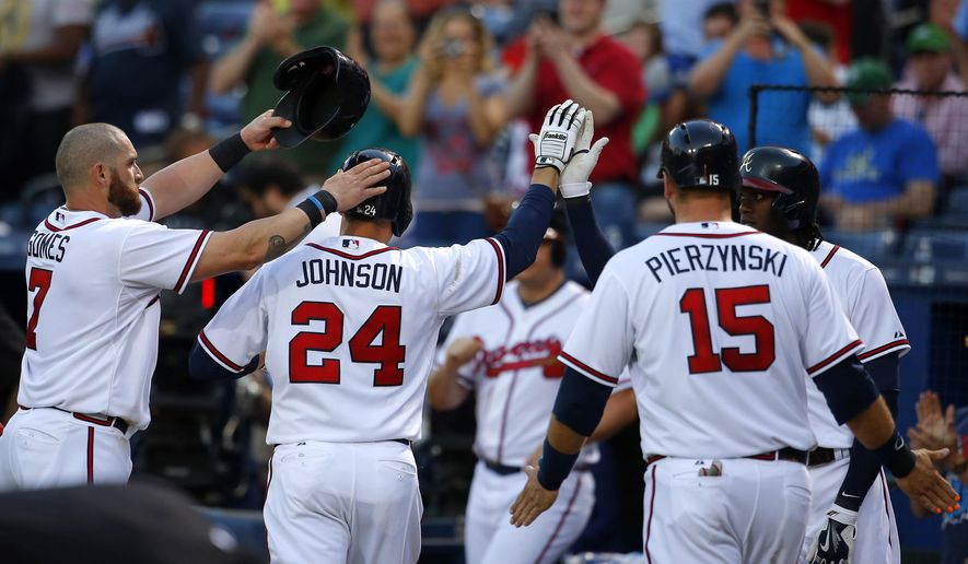 Atlanta Braves' Kelly Johnson (24) celebrates his three-run homer with Jonny Gomes, left, A.J. Pierzynski (15) and center fielder Cameron Maybin, right, in the fourth inning of a baseball game against the Philadelphia Phillies, Tuesday, May 5, 2015, in Atlanta. (AP Photo/Todd Kirkland)
