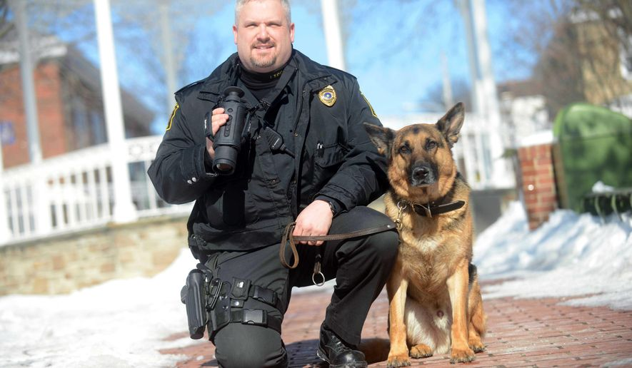 In this photo taken Monday, Feb. 24, 2015, Ligonier Township Lt. Eric Eslary, and his K-9 partner Blek, pose for a photo at the diamond in Ligonier, Pa. Eslary was killed while on patrol early Tuesday, May 5, 2015, in a head-on crash with a work van police say was traveling the wrong way.  Blek was taken to a veterinary hospital for surgery. Two men in the van were hospitalized with unspecified injuries (Evan Sanders/Tribune Review via AP) PITTSBURGH OUT