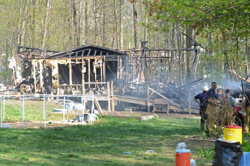 Chester County and Pennsylvania State Police Fire Marshals work on the scene of a deadly fire in the 300 block of Hill Road in West Caln on Monday, May 4, 2015. Three people were reported killed in the fire that started shortly after noon. (Vinny Tennis/Daily Local News via AP)